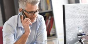 man speaking on the phone with a client | dedicated project management from web development company ABS in Bangalore India