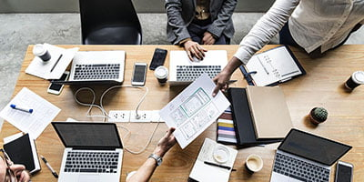 businessmen and a businesswoman discussing reposts in a meeting room top view at the office aerobusinesssolutions abs best search engine optimization seo company in bangalore india experienced team