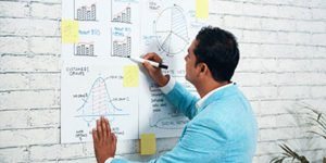 a man drawing reports and graphs and charts on a white sheet with a thick black marker on a white bricks wall in an office at www.aerobusinesssolutions.com results oriented seo company in bangalore india